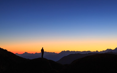 Fotomurales - Man looking at the colorful sky in the mountains during a tranquil dusk.