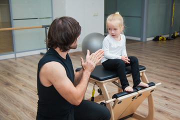 Pilates coach training child using special equipment.