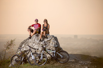 Cyclists are sitting on a large stone on the precipice of a cliff next to them are sports bikes. Blurred background with copy space