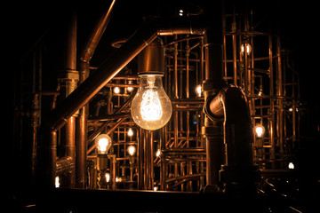 Light in darkness - Incandescent light bulb between rusty pipes