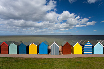 Row of beach huts on summer day with blue sky