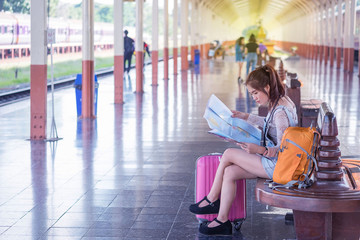 Young female traveler with luggage waiting by train and hold map