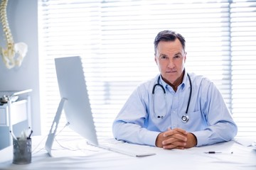 Portrait of male doctor sitting at desk