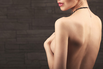 portrait of lovely naked woman covering her breast against beige