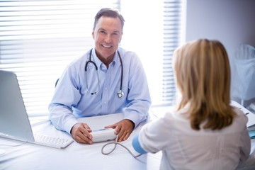 Portrait of doctor checking blood pressure of a patient