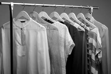 black and white photo of womens clothes on hangers. closet of wo