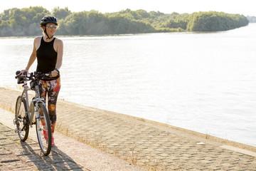 Young woman enjoying biking near the river
