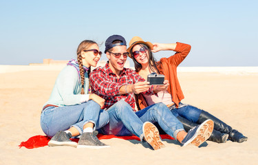 Group of friends taking selfie using old camera sitting on the beach in sunny spring break vacation day -  Concept of relax on the weekend