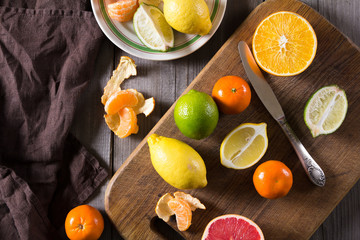 various types of citrus fruit on a dark wooden background