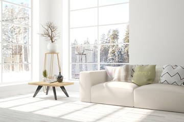 White interior design with sofa and winter landscape in window