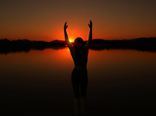 Silhouette of woman doing yoga at sunset