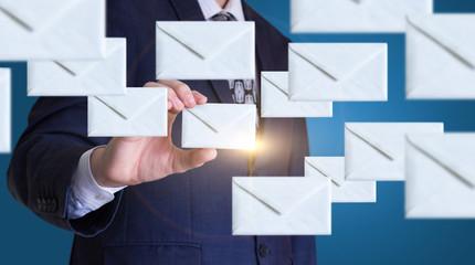 Businessman sends emails.