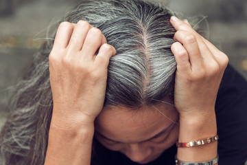 woman and gray hair with worried stressed face looking down