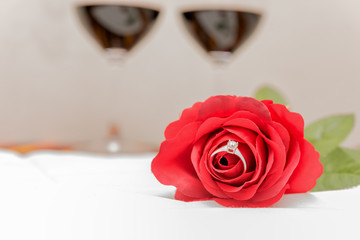 Diamond ring inside red rose over two wine glasses