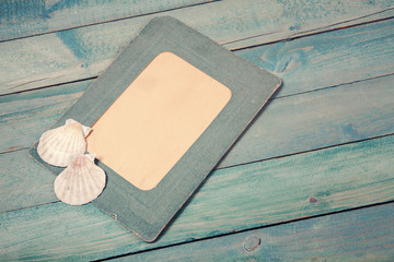 Old green photo frame with two sea shells
