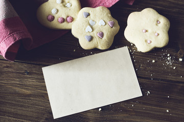 Homemade Decorated Cookies With Paper Card On Wooden Table.