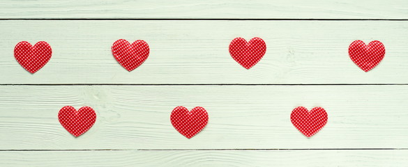red hearts symbol of love on a white wooden background