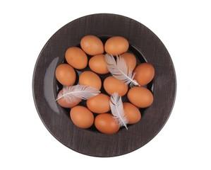 Braune Hühnereier mit Federn