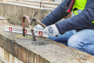 Construction worker working with hammer near concrete blocks