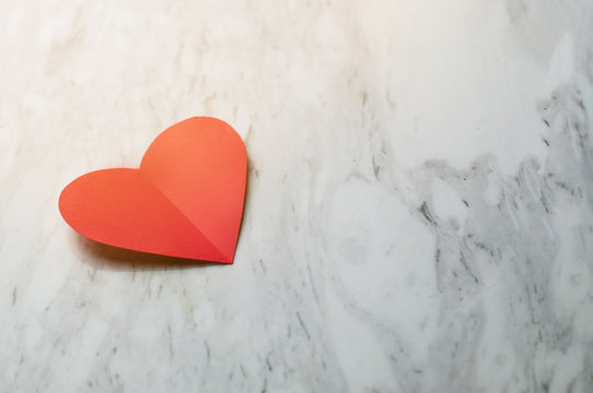 Red heart on white marble background.
