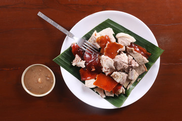 Flat Lay shot of [lechon or suckling pig chopped parts serve with banana leaf. The food is popular in Span and former Spanish colonial regions.