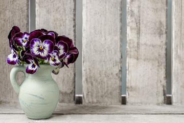 Foto auf Acrylglas Stiefmutterchen Bouquet of pansy flower in ceramic vase. Wooden background