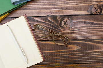 Open book, pen and glasses on a wooden table.