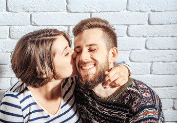 bearded man and pretty happy woman kiss on brick wall