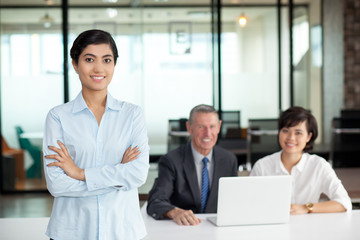 Smiling Asian woman in office with colleagues