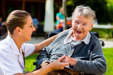 Pflegerin hält Schulter alter Frau im Rollstuhl