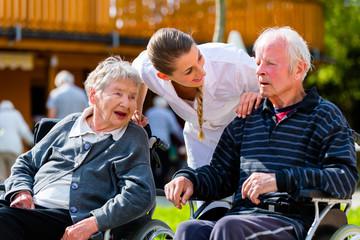Altes Paar im Garten von Altenheim mit Pflegerin