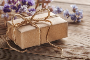 Gift box in kraft paper with bow on wooden background