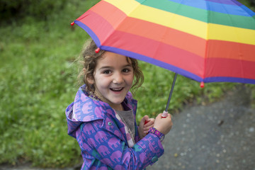 Girl holding rainbow umbrella and smiling