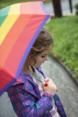 Girl holding rainbow umbrella