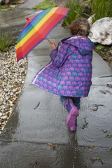 Girl running in rain with rainbow umbrella