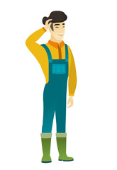 Young asian farmer in coveralls laughing.