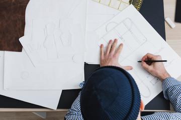 Unrecognizable male fashion designer working at a desk, high angle view.