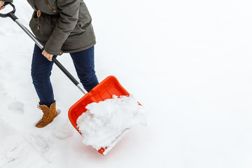 Woman with shovel cleaning snow. Winter shoveling. Removing snow after blizzard.