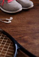 Fitness gym equipment. Tennis racket. Sneakers, music headphones and towel. Workout footwear. Grunge rustic wood background.