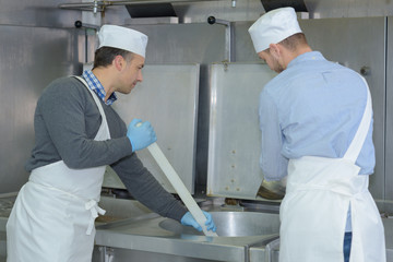 apprentice and chief preparing meat in restaurant kitchen