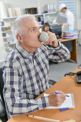Senior office worker enjoying a coffee