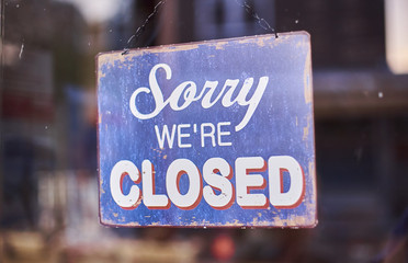 sorry we're closed shop sign hanging in a window