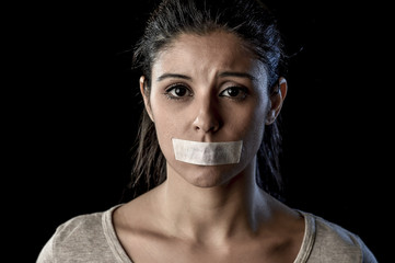 close up portrait of young attractive woman with mouth and lips sealed in adhesive tape restrained