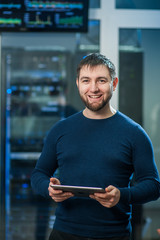 Young engineer businessman with the tablet in network server roo