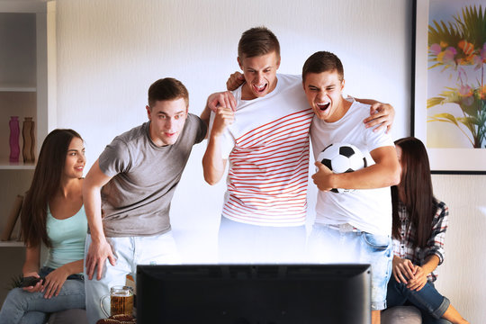 Young fans watching football match on TV