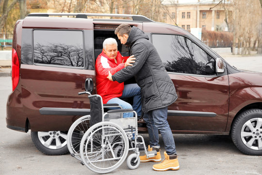 Young man helping handicapped man to sit in wheelchair