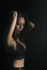 Sensual woman in sexy lace bra at the dark studio
