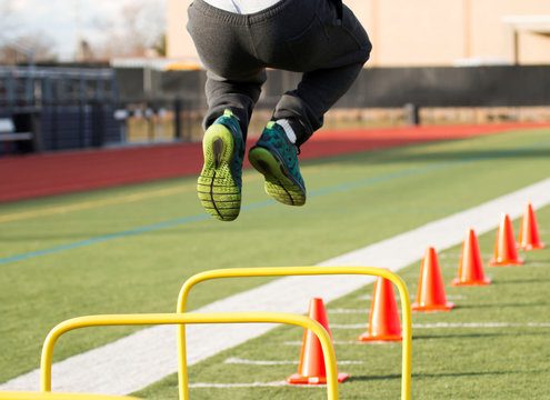Male athlete jumping over yellow hurdles