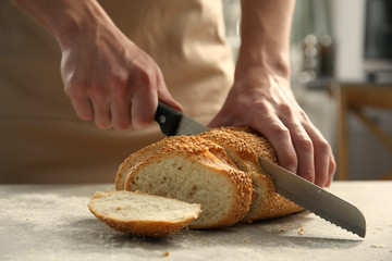 Male hands cutting wheaten bread, closeup