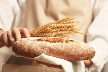Male hands holding freshly baked bread and wheat ears, closeup